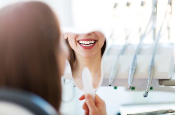 Woman looking at her smile in a mirror at Dynamic Dental Care in Spokane, WA